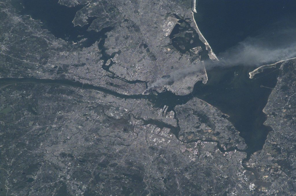 Visible from space, a smoke plume rises from the Manhattan area after two planes crashed into the towers of the World Trade Center. This photo was taken of metropolitan New York City (and other parts of New York as well as New Jersey) the morning of September 11, 2001. Credits: NASA